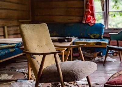 En stue vis-a-vis kjøkkenet bærer preg av å ha hatt gjester etter at huset ble fraflyttet.